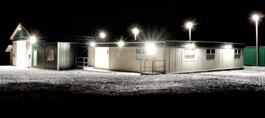 Warehouse with bright lights outside surrounding buildings and bay doors open with light spilling outside from inside Full NightRider Commercial Lighting Indoor/Outdoor